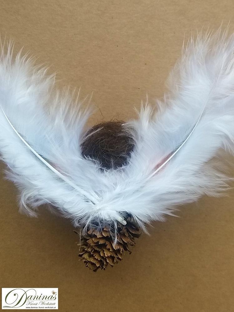 Schutzengel Peachy, Rückseite. Handgefertige Figur aus Lärchenzapfen mit braunen Haaren und buntem Haarband aus Wolle sowie bunten und weißen Federnflügeln.