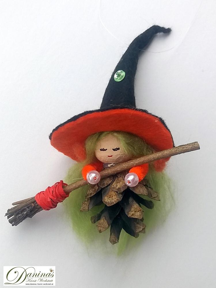Hexe Hella. Handgefertigte Figur aus Kiefernzapfen, mit grünen langen Haaren aus Wolle, einem schwarz-orangen Hexenhut aus Filz mit einem magischen grünen Stein und einem Hexenbesen aus Zweigen