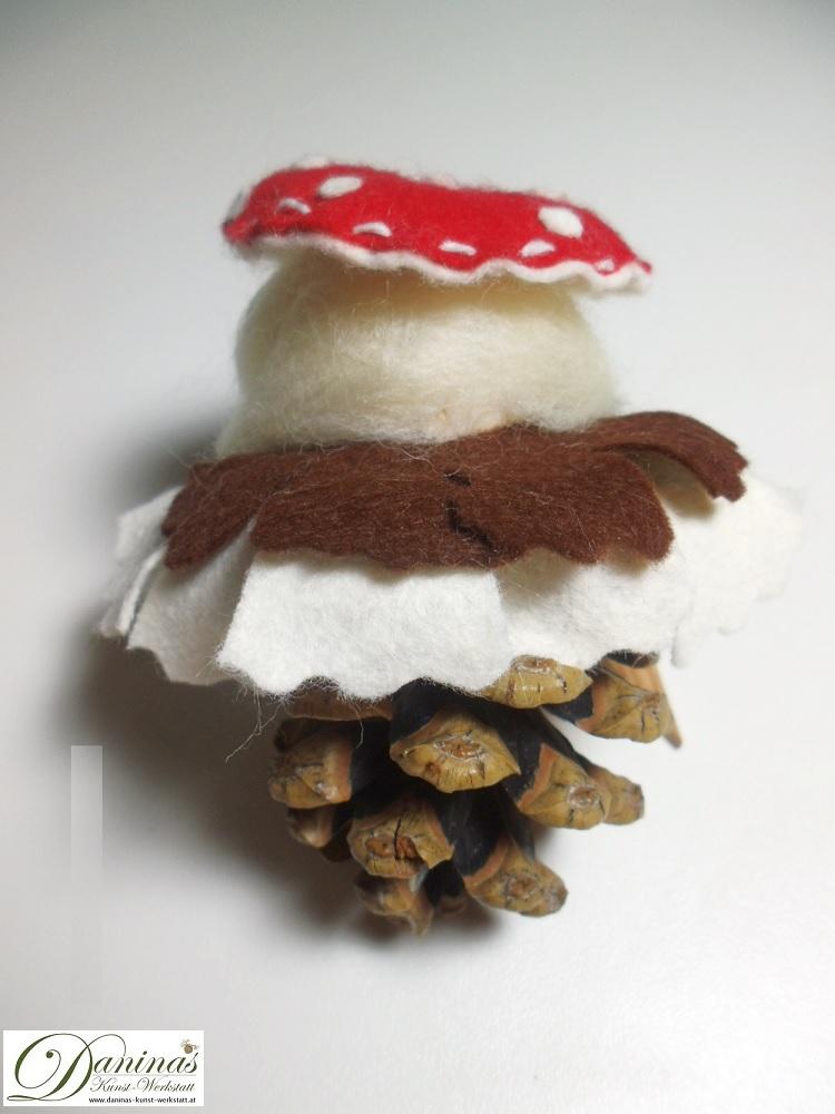 Waldelfe Frau Glückspilz, Rückseite. Handgefertigte Figur aus Kiefernzapfen mit dicken Zöpfen aus Wolle, Fliegenpilz Hut und Mantel aus Filz