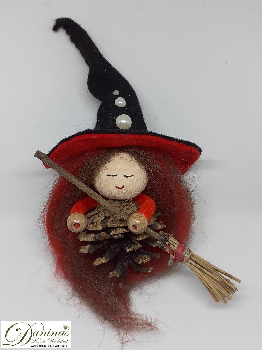 Hexe Crystella. Handgefertigte Figur aus Kiefernzapfen, mit rot-braunen langen Haaren aus Wolle und schwarz-orangem Hexenhut aus Filz mit Zierperlen, Hexenbesen aus Kiefernnadeln