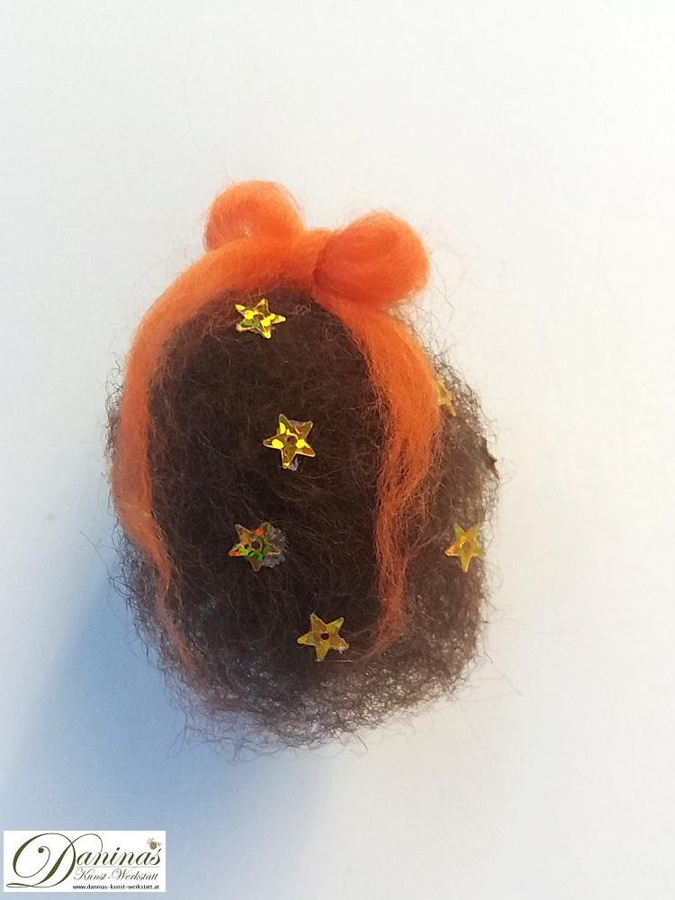 Kleine Hexe Stella, Rückseite. Handgefertigte Figur aus Kiefernzapfen, mit braunen langen Haaren aus Wolle mit Sternen und einem orangen Haarband, grüne und orange Bommeln im Zapfen