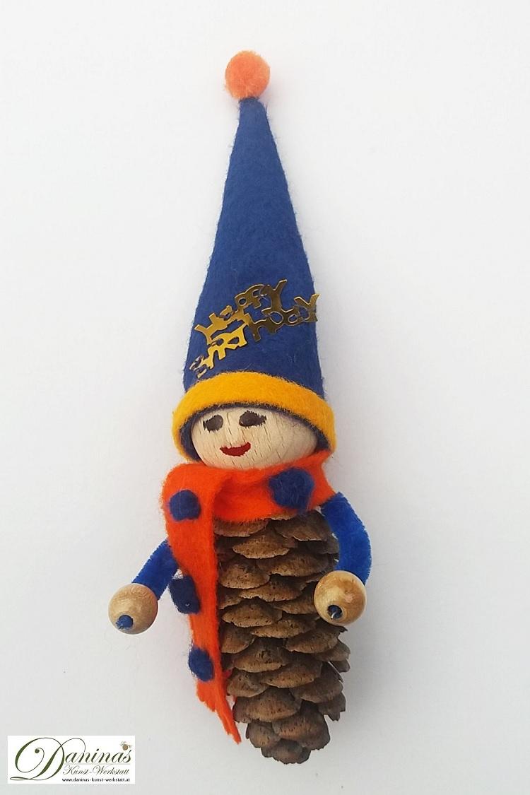 Geburtstagswichtel Benno. Handgefertigte Figur aus Fichtenzapfen, mit orangem Schal und blauer Zipfelmütze aus Filz mit blau-orangen Bommeln