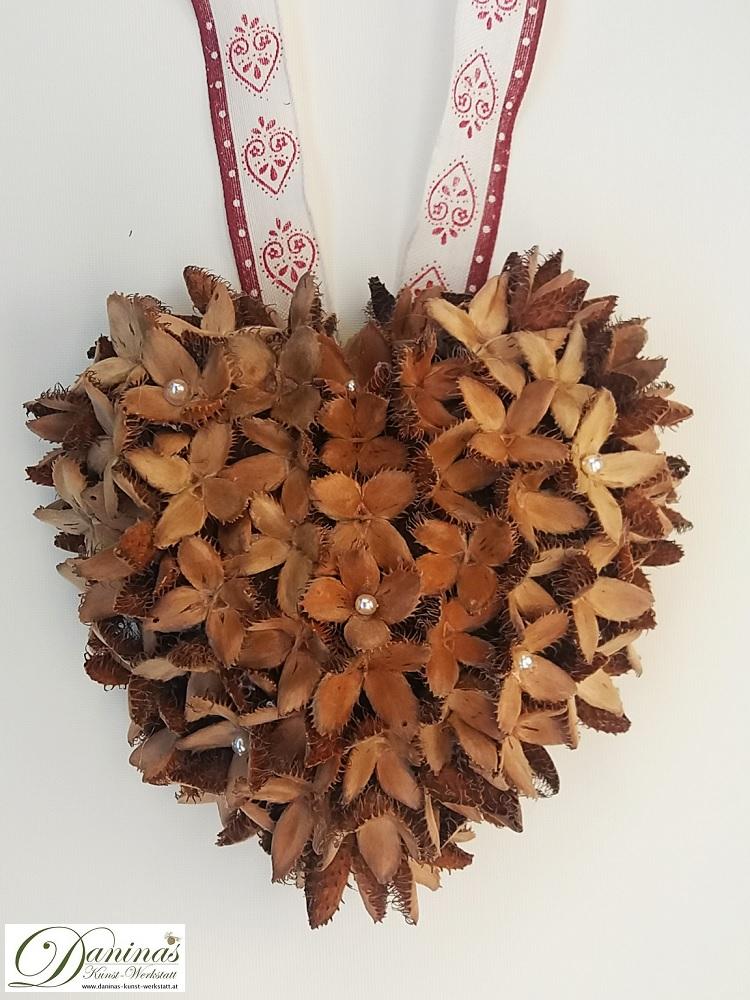 Handgefertigtes Dekoherz aus Bucheckern mit Perlen und ecru-rotem Zierband. Ideal als Geschenk oder Herbstdeko.