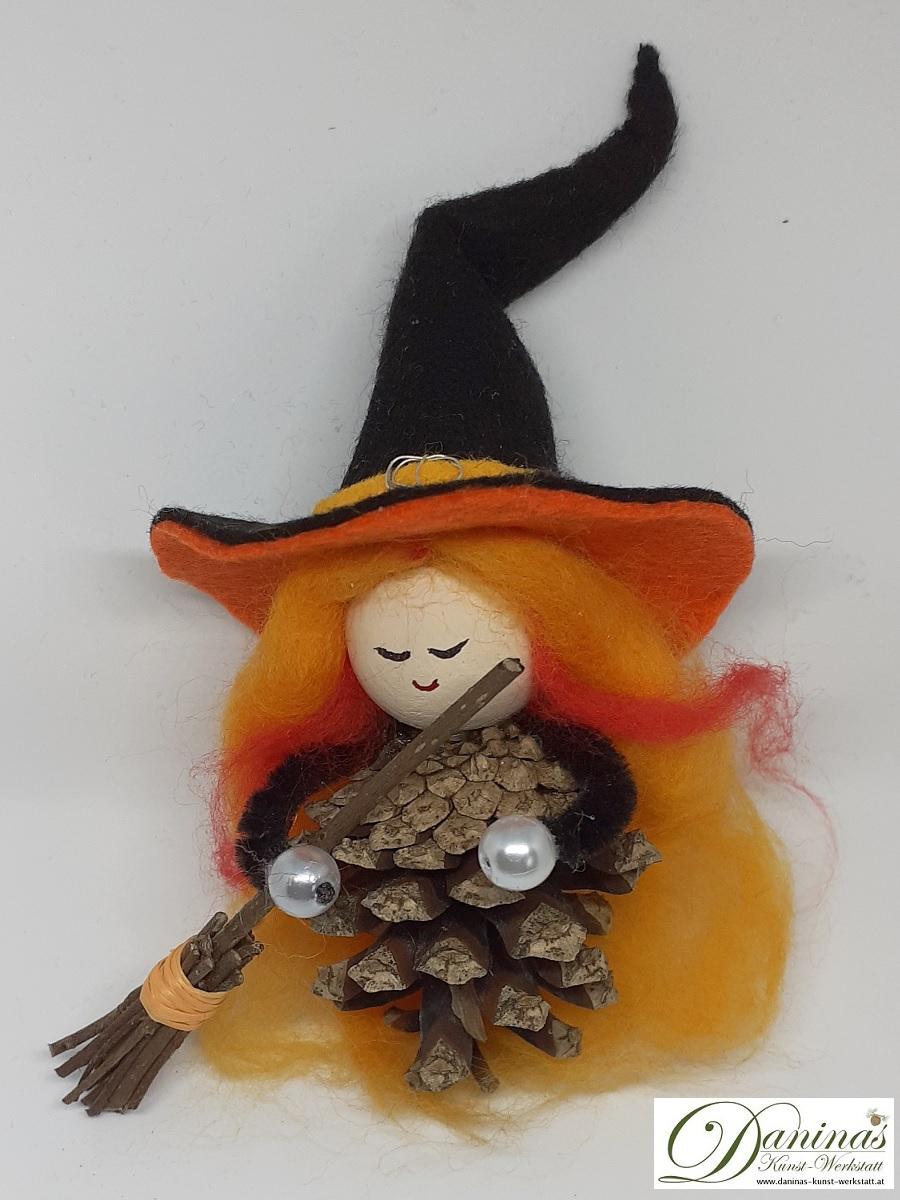 Hexe Lemona. Handgefertigte Märchenfigur aus Kiefernzapfen, mit blond-orangen langen Haaren aus Wolle, schwarz-orangefärbigem Hexenhut aus Filz und Hexenbesen aus Haselnusszweigen