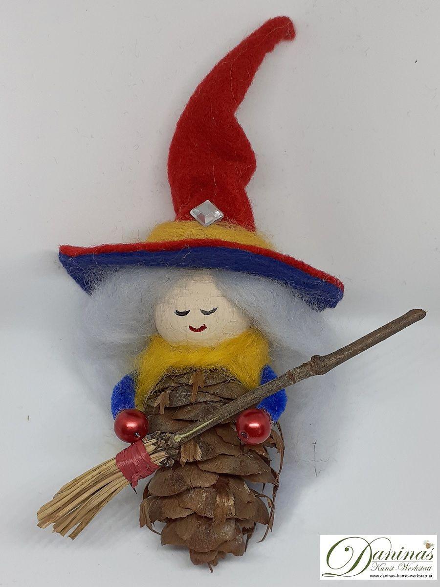 Hexe Aurora. Handgefertigte Märchenfigur aus Douglasienzapfen, mit zartblauen langen Haaren aus Wolle, rot-blauen Hexenhut aus Filz, gelben Jäckchen, Hexenbesen aus Zweigen
