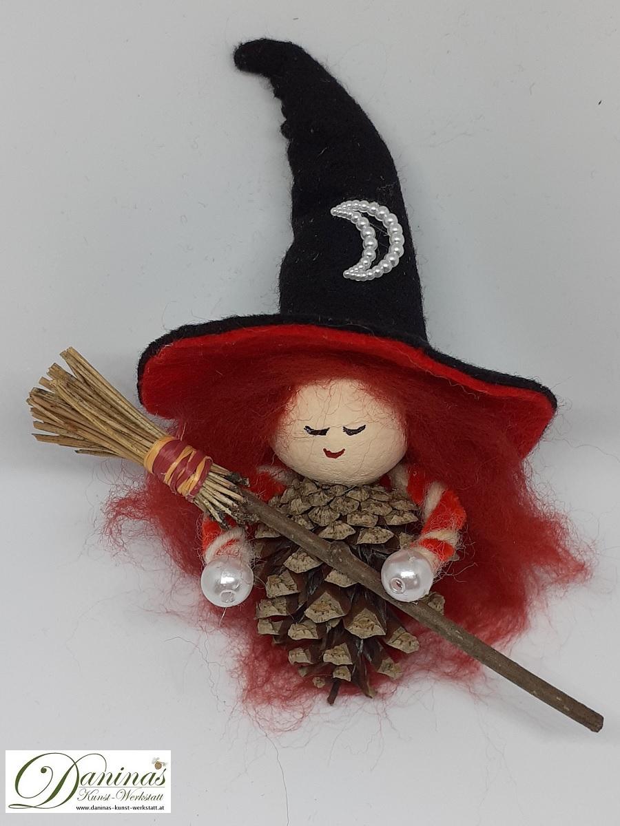Hexe Astra. Handgefertigte Figur aus Kiefernzapfen, mit rostbraunen langen Haaren aus Wolle, einem schwarz-orangen Hexenhut aus Filz mit Perlenmond und einem Hexenbesen aus Kiefernnadeln