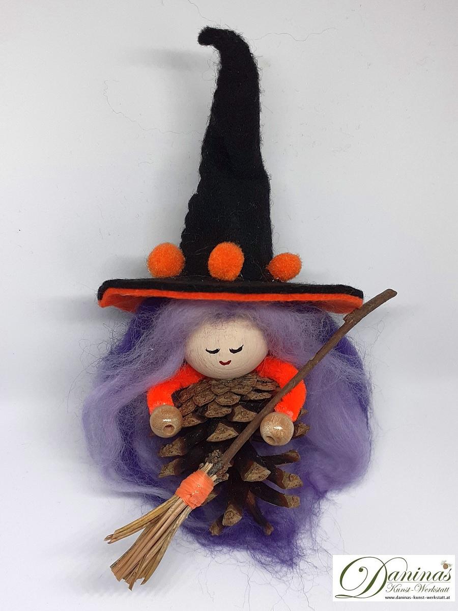 Hexe Holunda. Handgefertigte Figur aus Kiefernzapfen, mit violett-lila langen Haaren aus Wolle und schwarz-orangem Hexenhut aus Filz, Hexenbesen aus Kiefernnadeln