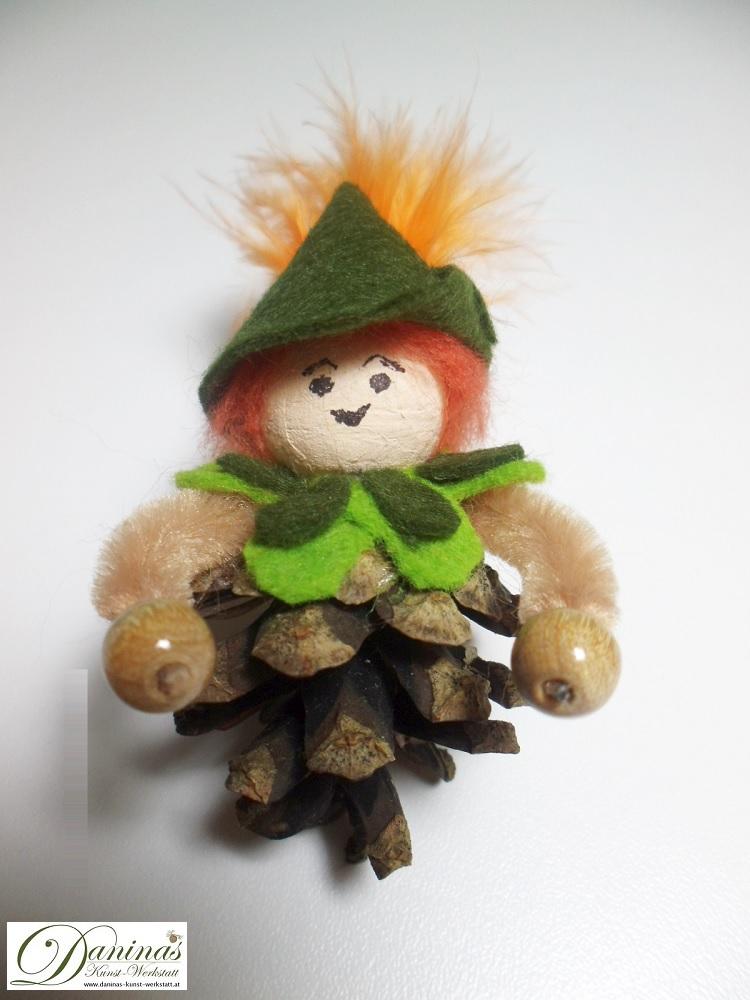 Peter Pan. Handgefertigte Figur aus Kiefernzapfen mit einem Jäckchen und Hut aus grünem Filz mit einer orangen Feder.