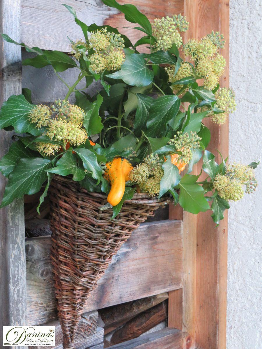 Herbstdeko Idee #3: Rattan-Füllhorn mit orange/gelben Kürbissen und blühendem Efeu