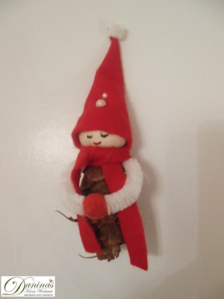 Wichtel Blasius, Rückseite. Handgefertigte Figur aus Douglasienzapfen, mit Schal und Zipfelmütze aus rotem Filz mit weißem Bommel