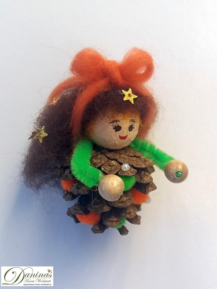 Kleine Hexe Stella. Handgefertigte Figur aus Kiefernzapfen, mit braunen langen Haaren aus Wolle mit Sternen und einem orangen Haarband, grüne und orange Bommeln im Zapfen