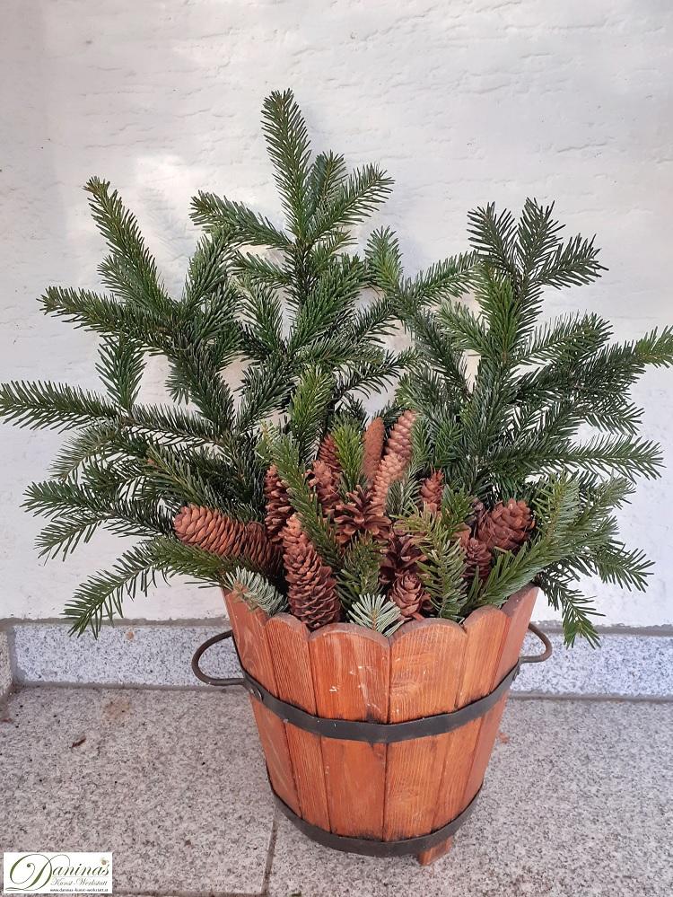 Winterliches Gesteck aus Tannenzweigen und Zapfen im Holzfass für die Terrasse
