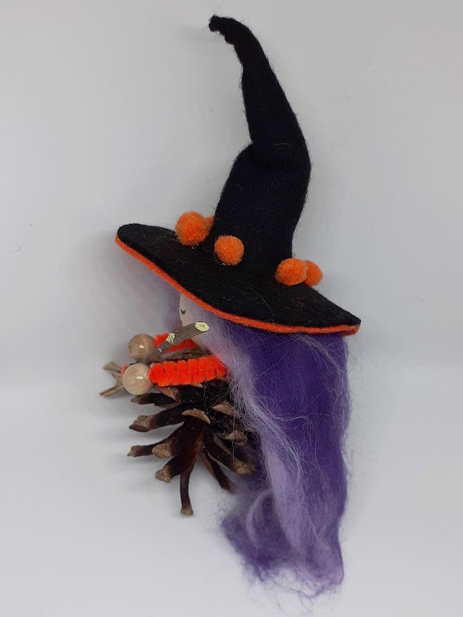 Hexe Holunda Seitenansicht. Handgefertigte Figur aus Kiefernzapfen, mit violett-lila langen Haaren aus Wolle und schwarz-orangem Hexenhut aus Filz, Hexenbesen aus Kiefernnadeln