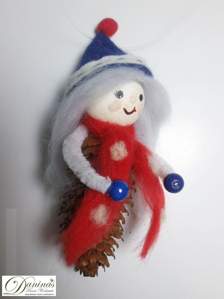 Winterfee Lauriel. Handgefertigte Figur aus Fichtenzapfen, mit hellblauen langen Haaren und einem roten Schal aus Wolle sowie einer dunkelblauen Filzmütze.