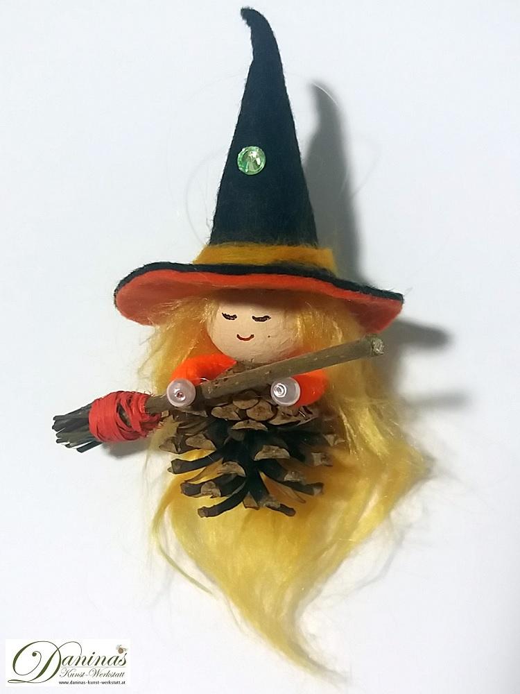 Hexe Kala. Handgefertigte Märchenfigur aus Kiefernzapfen, mit blonden langen Haaren aus Wolle, einem schwarz-orangen Hexenhut aus Filz und einem Hexenbesen aus Zweigen
