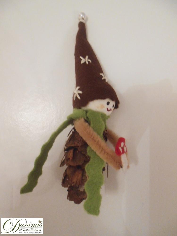 Glückswichtel Benjamin Pilz, Rückseite. Handgemachte Figur aus Douglasienzapfen, mit grünem Schal, brauner bestickter Zipfelmütze und einem Fliegenpilz aus Filz.