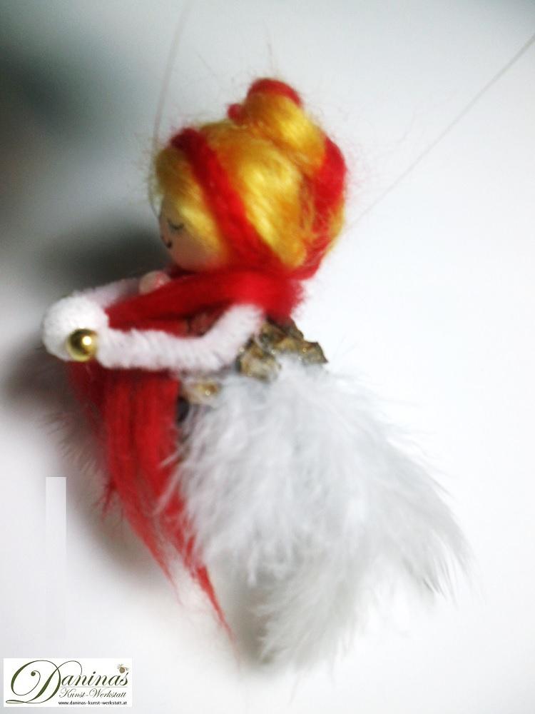 Winterfee Schneeflocke. Handgefertigte Figur aus Kiefernzapfen, mit goldenen Haaren und rotem Schal aus Wolle, weißen Federnflügeln und einem Schneeball.
