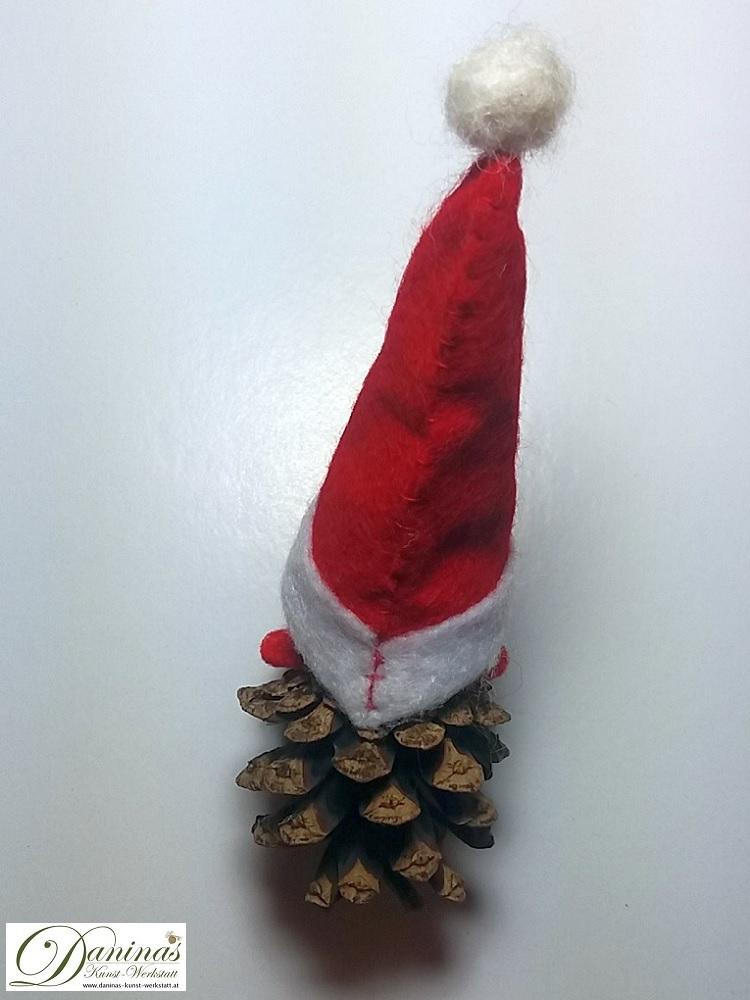 Weihnachtswichtel Bringfreud, Rückseite. Handgemachte Märchenfigur aus Kiefernzapfen, mit braunen Haaren aus Wolle, rot-weißer Zipfelmütze  und weißem Schal aus Filz