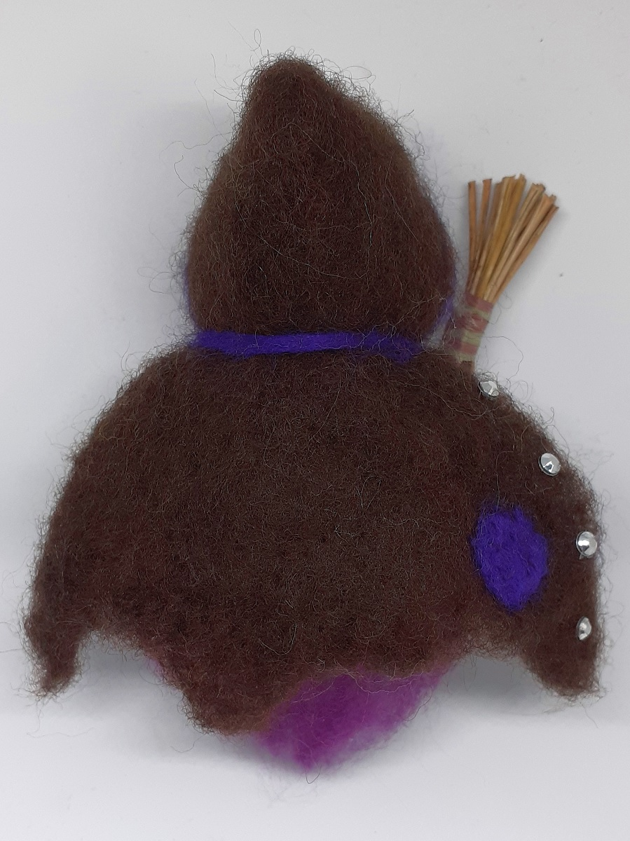 Hexe Viola Rückseite. Handgefertigte Figur aus Kiefernzapfen, mit violetten langen Haaren und nadelgefilztem braunen Hexenmantel aus Wolle, silberne Ziersteinen, Hexenbesen aus Kiefernnadeln