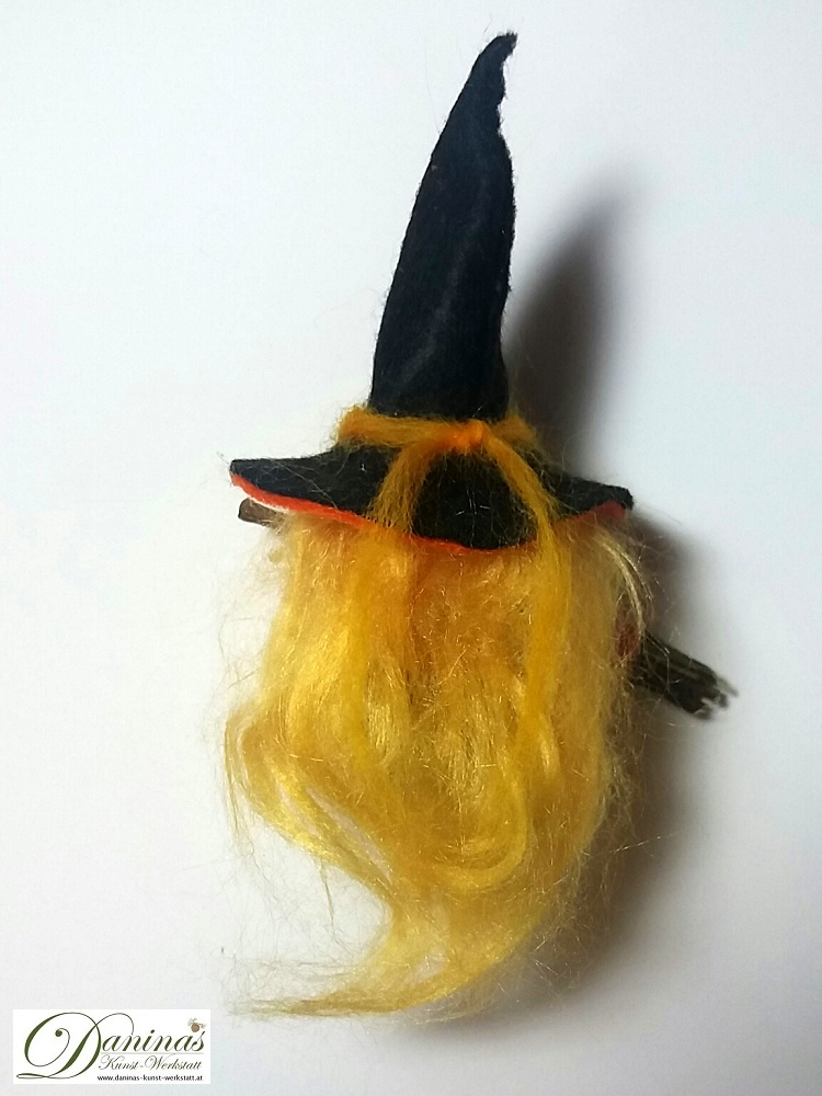 Hexe Kala, Rückseite. Handgefertigte Figur aus Kiefernzapfen, mit blonden langen Haaren aus Wolle, einem schwarz-orangen Hexenhut aus Filz und einem Hexenbesen aus Zweigen