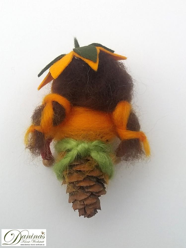 Blumenfee Echinacea, Rückseite. Handgefertigte Figur aus Douglasienzapfen, mit langen braunen Zöpfen und einem orange-grünen Jäckchen aus Wolle sowie einem Blütenhut aus Filz
