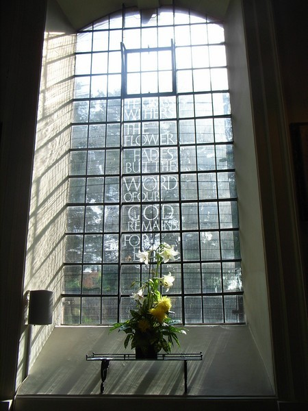 The dark Victorian patterned glass was replaced c1960s by plain clear glass. This etched design commemorates the life of a member of the church who died c1980.
