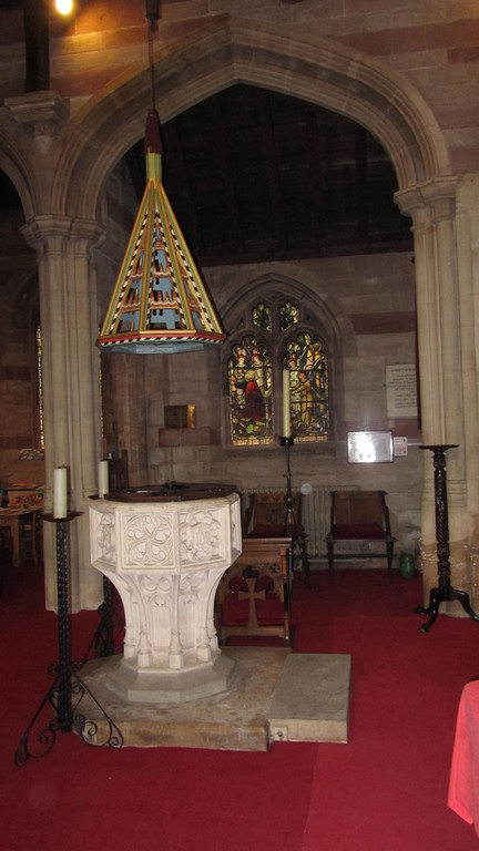 The 19th-century font at the west end of the nave