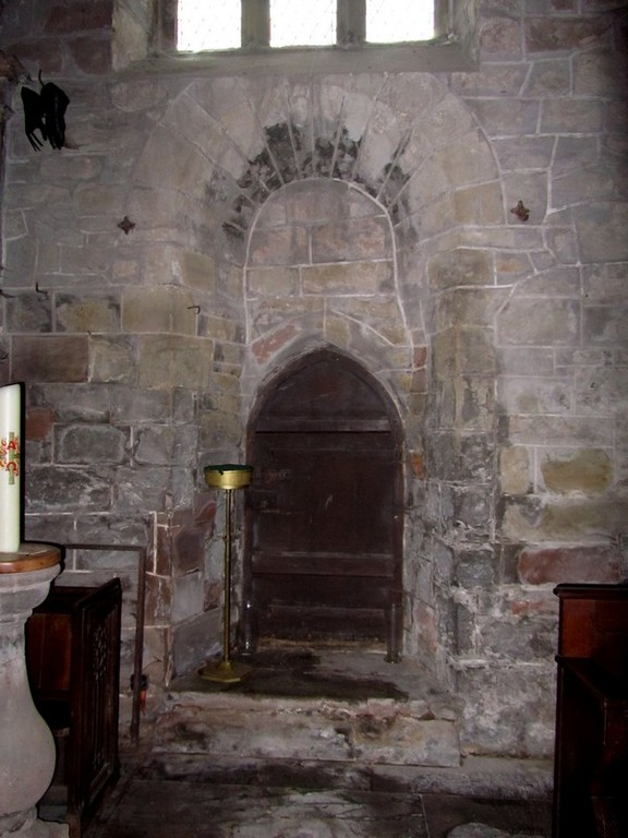 14th-century priest's door in the south wall of the chancel, blocked 12th-century window above