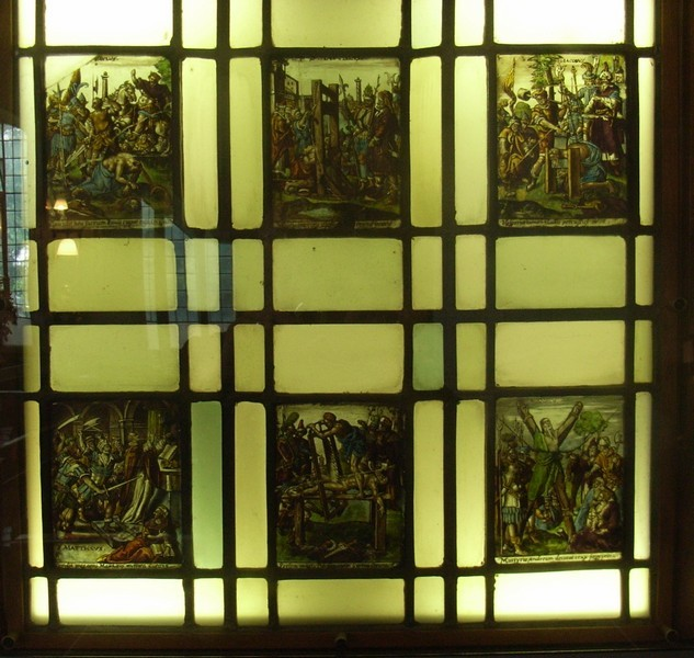 Some old glass is displayed on the north wall by the entrance to the Foden Room. It is Flemish c1590 of very good quality and fine detail. A series shows the gruesome deaths of some of the Church's martyr saints. It came here from Castle Bromwich Hall.