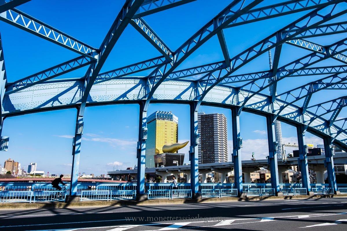 """Tokyo , le pont bleu dans le quartier Asakusa. La tour de la bière Asahi avec une """"flamme jaune au sommet, sensé représenter la mousse de la bière"""