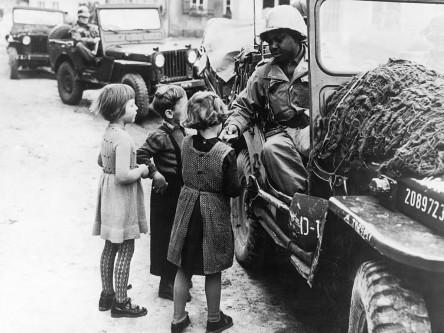 Ein amerikanischer Soldat schenkt Kindern Schokolade