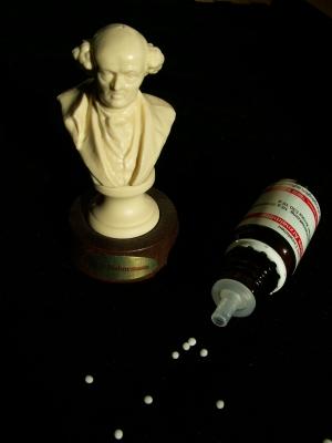 Foto einer liegenden Flasche, aus welcher homöopathische Mittel rollen. Daneben eine Büste Samuel Hahnemanns, dem Begründer der Homöopathie.