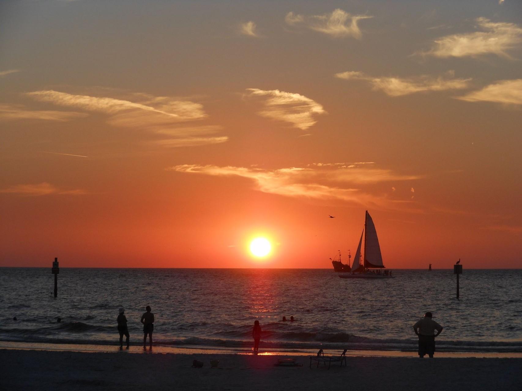Sonnenuntergang am Strand, mit Windsurfer und Piratenschiff im Hintergrund (leider keine Delfine gesehen)