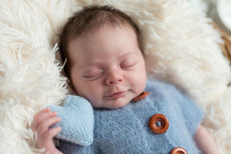 Newbornfotoshooting Bub mit blauen Strampler