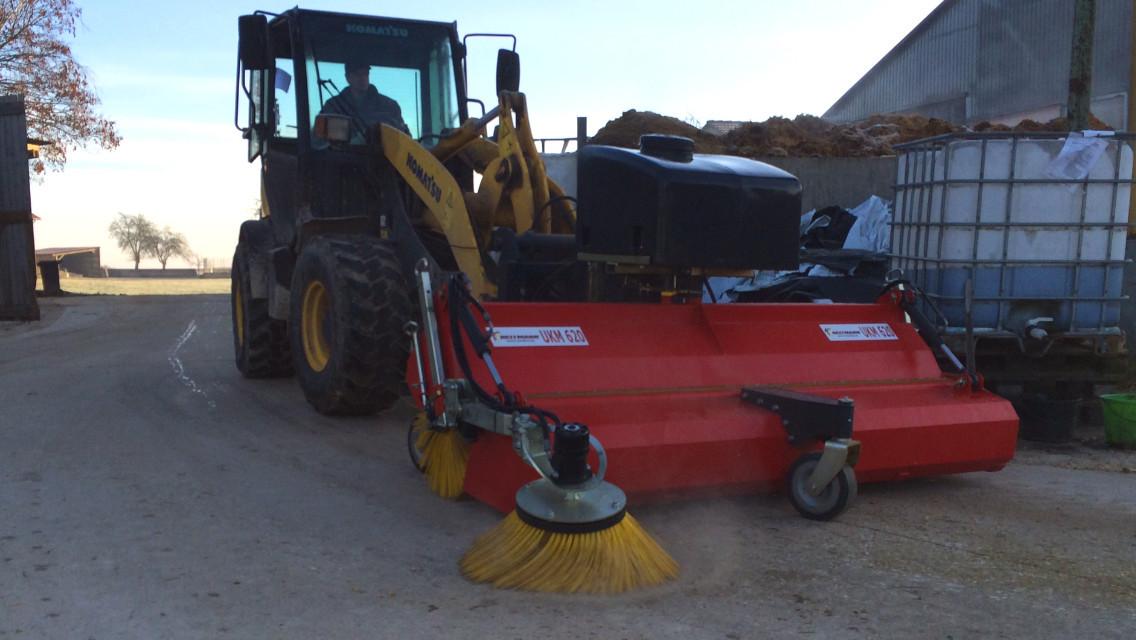 UKM 620 am Komat´su mit Seitenbesen und Wassersprüheinrichtung für nahezu staubfreies Kehren