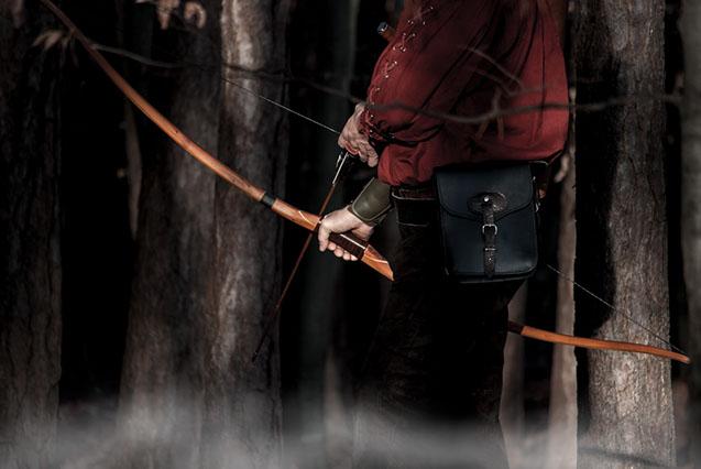 Recurvebogen mit Bambuspfeile beim Bogenschießen im Wald.