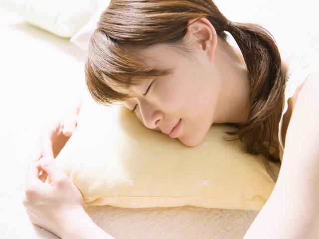 枕を抱えて眠る女性の写真