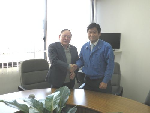 高村事務局長(右)と固い握手を交わす岩本理事長(左