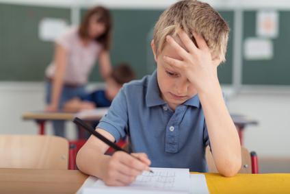 Junge, Bub in der Schule, Bub schreibt, Bub überlegt, Konzentrieren
