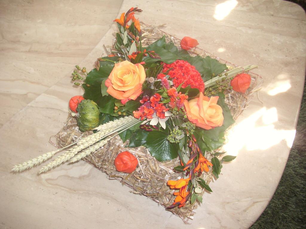Herbstgesteck in einem  Strohpäckli Ären, orange Rosen,Moonpretien,Lampions