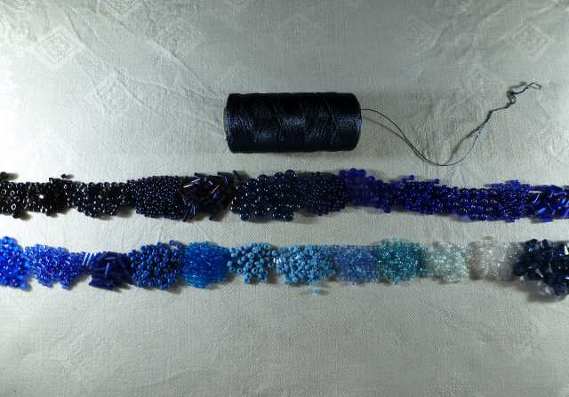 2. Schütten Sie eine kleine Menge jeder Farbe in der richtigen Reihenfolge auf eine Stoffunterlage. Ehe Sie häkeln können, müssen die Perlen auf das Garn gefädelt werden.