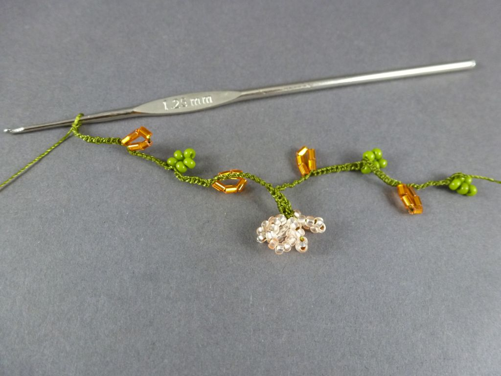 15. Häkeln Sie 10 LM, 5 orange Perlen, 10 LM, 5 grüne Perlen, 10 LM, 5 orange Perlen, 15 LM, danach die nächste Blüte.