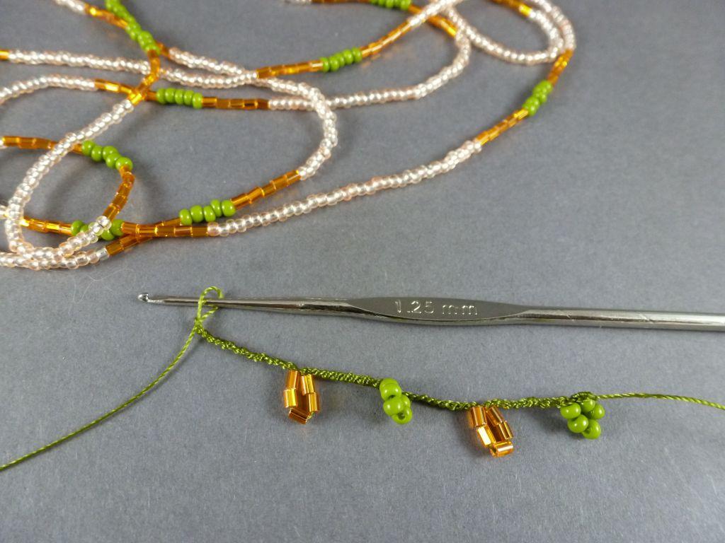 10. Häkeln Sie 10 Luftmaschen, dann die nächsten 5 grünen Perlen, 10 Luftmaschen, danach die orangen Perlen.