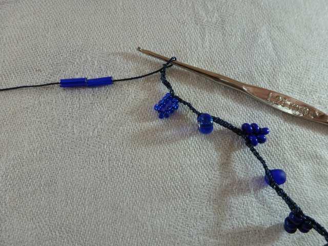 16. Wiederholen Sie dies, bis Sie den ersten Strang gehäkelt haben: abwechselnd die Perlen einer Farbe in eine Luftmasche einhäkeln, dann 1cm leere Luftmaschen etc. Stoppen Sie, wenn Sie wieder bei Farbe 1 angekommen sind.