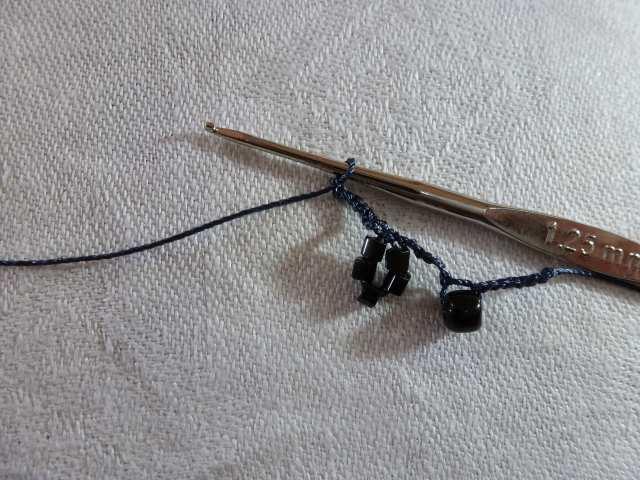 15. Nachdem das Perlengrüppchen eingehäkelt ist, bildet es ein kleines Blümchen. Zum Abschluß häkeln Sie noch einmal 1cm Luftmaschen.