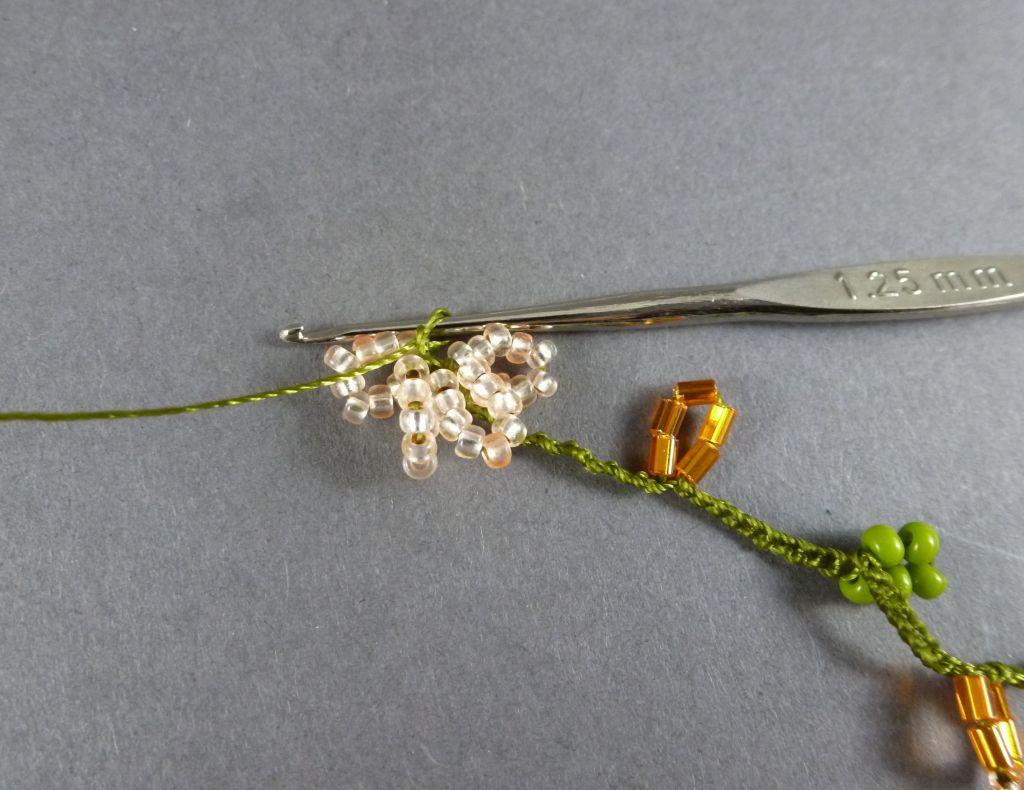 13. Wiederholen Sie Schritt 12, bis Sie 4 apricotfarbene Perlenbögen (=Blütenblätter) gehäkelt haben.