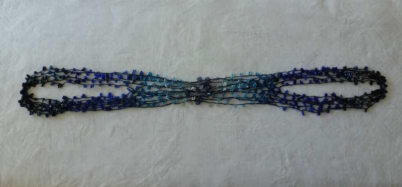 28. Legen Sie die Anfänge und Enden übereinander, so daß immer dieselben Perlen übereinander zu liegen kommen. Halten Sie einen Abstand zwischen der oberen und unteren Hälfte der Kette. In der Mitte gehen die Stränge über Kreuz, das ist normal.