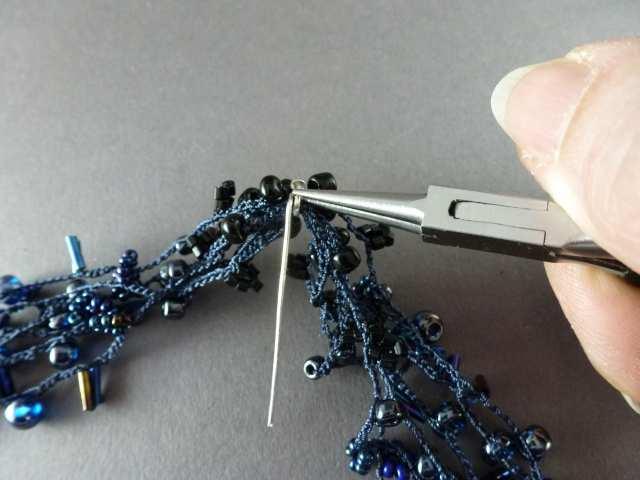 32. Halten Sie den Stift mit einer Zange fest und biegen Sie das gerade Ende des Stiftes 2-3mal um alle Stränge, immer an derselben Stelle. Achten Sie darauf, keine Perlen einzuklemmen.