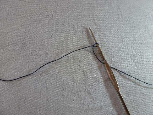 6. Nun geht es ans Häkeln. Entfernen Sie die Fädelnadel vom Garn. Dort, wo die Nadel war, beginnen Sie mit dem Häkeln. Nehmen Sie eine Häkelnadel der Stärke 1,25mm und schlagen Sie ca. 10cm vom Fadenende entfernt eine Masche an.