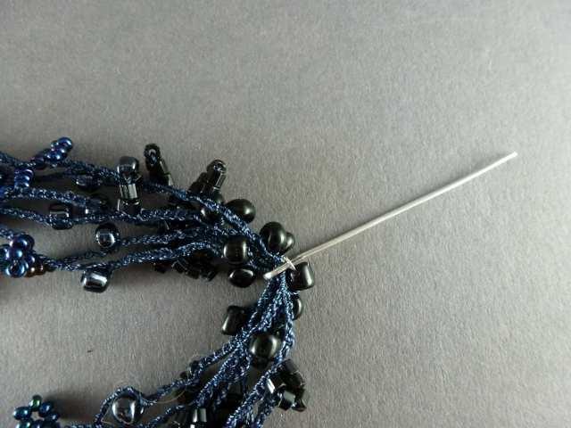 31. Hängen Sie alle gehäkelten Stränge in den Haken, so daß die Perlen der Farbe 1 jeweils rechts und links des Stiftes zu liegen kommen.